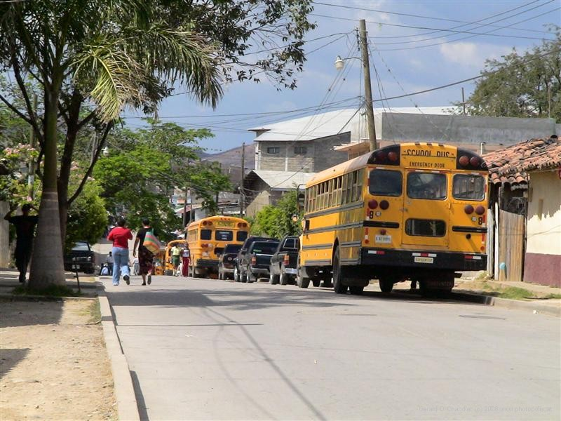 Former American school buses on a street in Comayagua